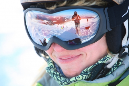 goggles:  Closeup portrait of a female skier standing on a skiing slope