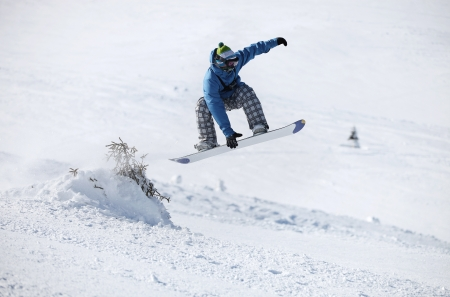 Young male snowboarder jumping on a snowy slope photo
