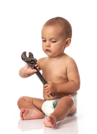 Cute little boy holding an adjustable spanner over white Stock Photo - 17343953