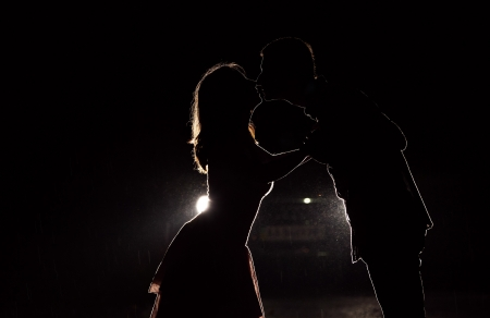 Silhouette of a young couple in the dark against car headlights  photo