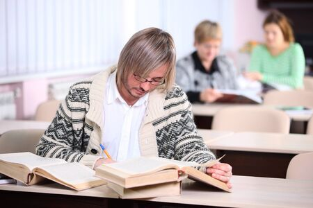 Handsome man studying while sitting at desk with lot of books  Stock Photo - 17570897