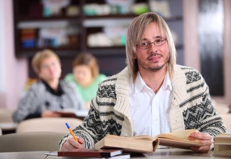 Handsome man studying at desk with lots of books Stock Photo - 17570901