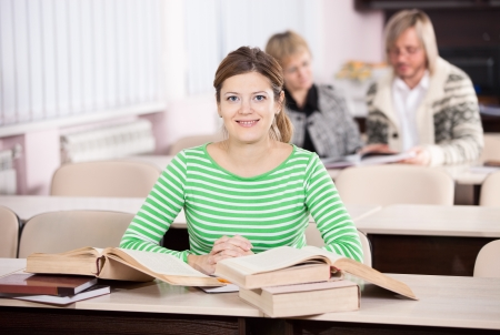 Young woman studying at desk with lots of books  Stock Photo - 17574530
