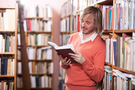 Handsome man reading book in library Stock Photo - 17570910