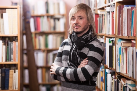 single shelf: Handsome man looking at camera while standing in aisle in library