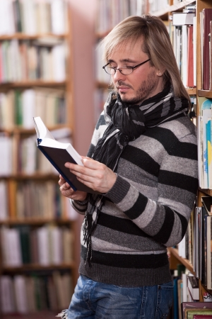 Handsome man reading book in library Stock Photo - 17570912