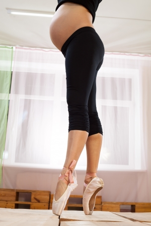Lower half waist down image of young pregnant woman on pointe photo