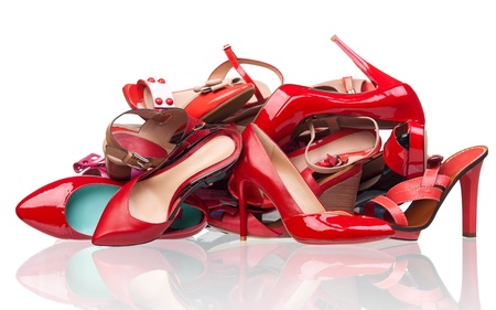 patent leather: Pile of various red female shoes over white Stock Photo