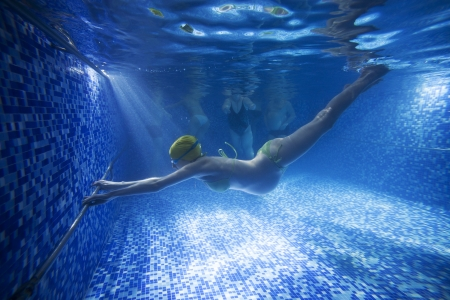 oung pregnant woman underwater in swimming pool  photo