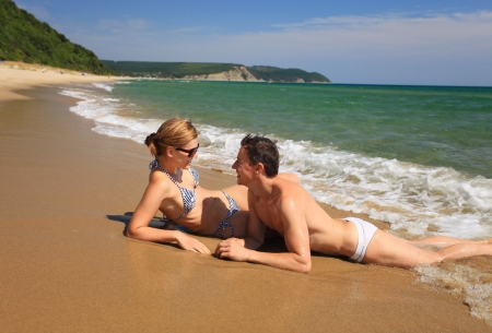 Young caucasian couple sunbathing at the beach photo
