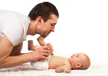 Young Caucasian father playing with baby son ower white background