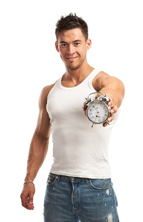 handsome young athletic: Cropped view of a muscular young man holding clock over white background  It is time for workout concept