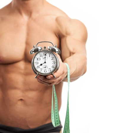 fit on: Cropped view of a muscular young man holding clock and measuring tape over white background  It is high time for workout concept  Stock Photo