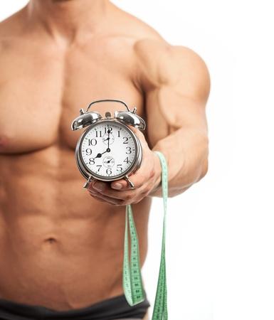 hombre fuerte: Recorta la vista de un hombre musculoso joven que sostiene el reloj y la medición de cinta sobre fondo blanco Es hora de que el concepto de entrenamiento Foto de archivo