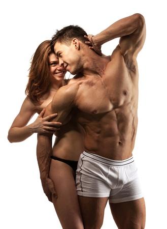 pareja apasionada: Hermosa joven pareja atlética sobre fondo blanco