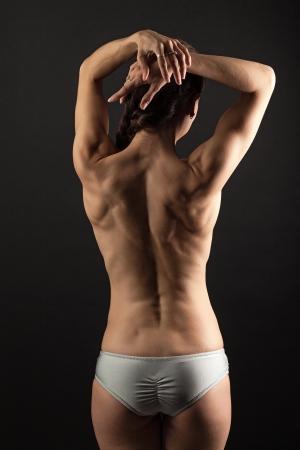 nalga: Vista posterior de la joven mujer de la aptitud sobre el fondo negro