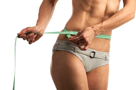 Cropped view of young fitness woman with measuring tape over white background photo