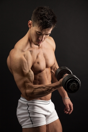 Muscular young man lifting a dumbbell over black background photo