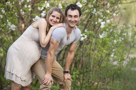 Young pregnant couple outdoors in spring blossom photo
