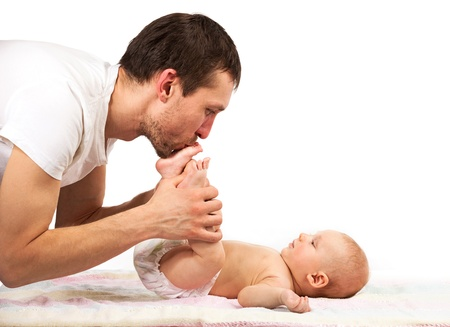 Young caucasian father kissing feet of his baby son Stock Photo