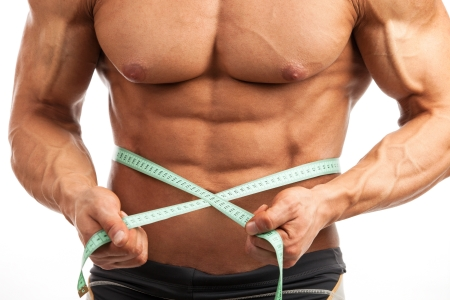 Cropped view of young muscular man with measuring tape