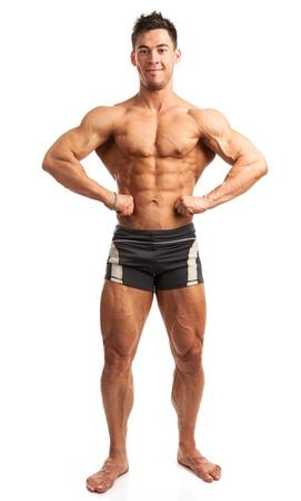 culturista: Bodybuilder joven posando aislados sobre fondo blanco