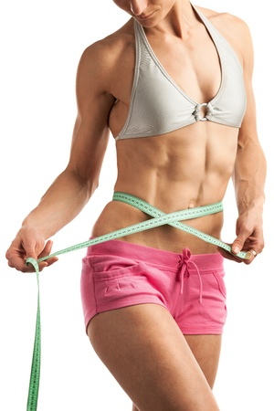 Young fitness woman with measuring tape over white photo