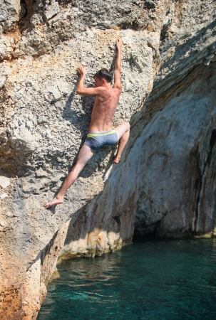 Deep water soloing, male rock climber on cliff photo