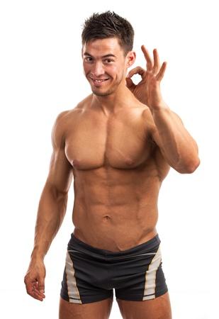 Muscoloso giovane uomo che mostra il segno ok isolato su bianco