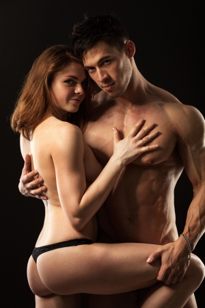sexy male model: Beautiful young athletic couple over black background Stock Photo