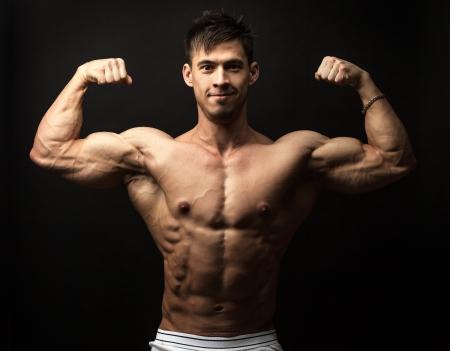 waistup: Retrato Cintura-para arriba de hombre musculoso flexionando sus b�ceps