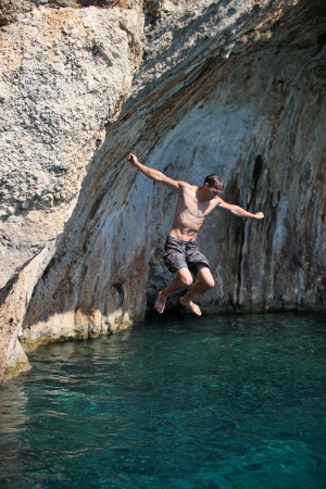 Young man jumping from cliff into sea photo