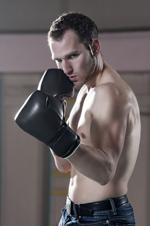 Waist-up of young male boxer in gym photo