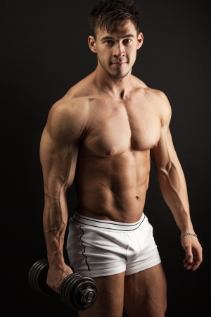 Muscular young man with a dumbbell over black photo