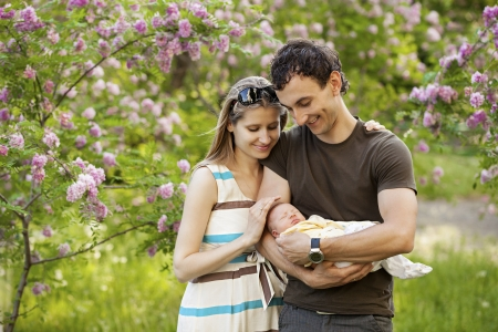 Young couple with newborn son outdoors in spring photo