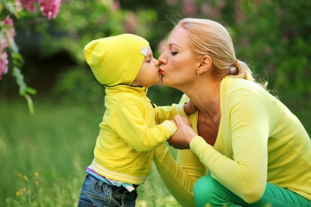 mom kiss son: Little boy kissing his young mother outdoors