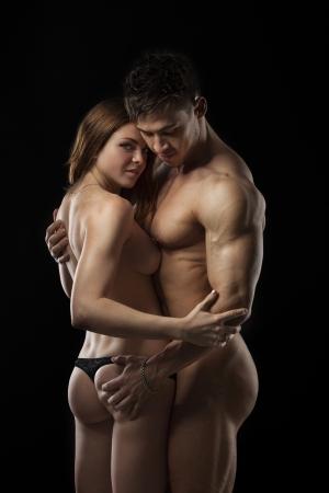 cuerpos desnudos: Hermosa joven atlético sexy sobre fondo negro Foto de archivo