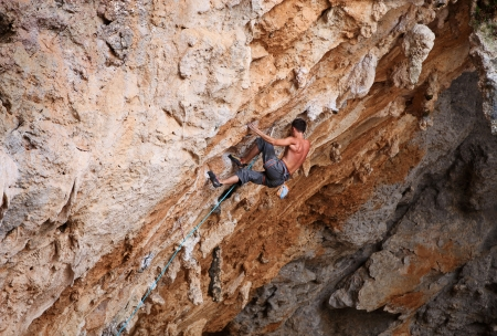Male rock climber struggling his way up Stock Photo - 20593244
