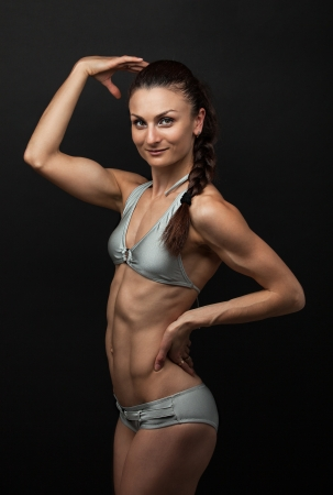 Young fitness woman in bikini flexing bicep photo