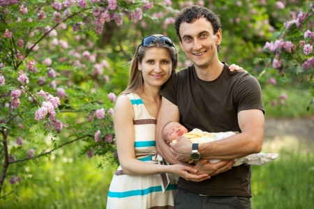 Young caucasian couple with newborn son outdoors in spring photo