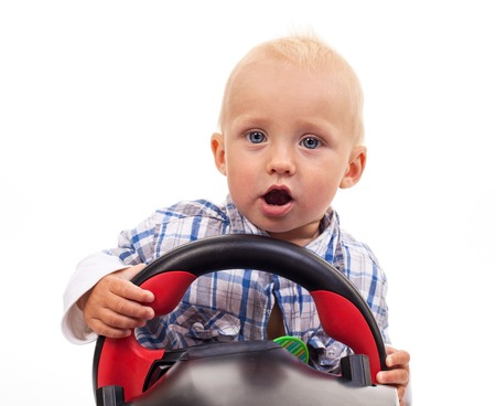 Little boy holding a toy steering wheel over white background photo