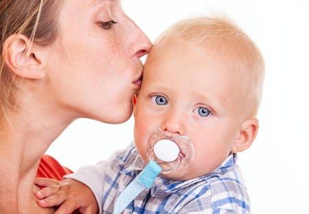 Young Caucasian woman kissing her baby son over white, closeup view photo