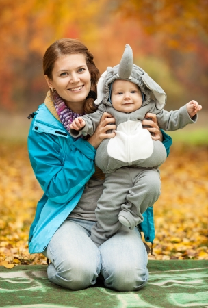 Portrait of young woman and her baby boy dressed in elephant costume in autumn park photo