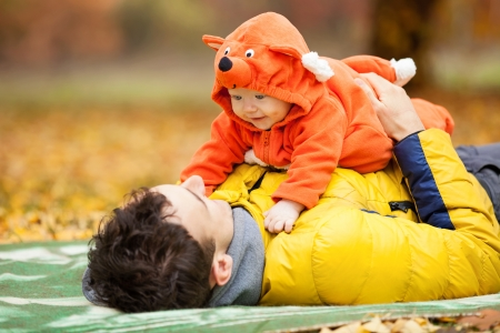 Young father and his little son in fox costume having fun in autumn park photo