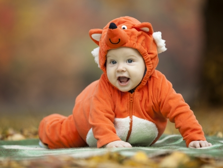 Baby boy dressed in fox costume in autumn park photo