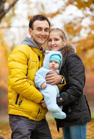 Young couple with baby boy on looking at camera in autumn park photo