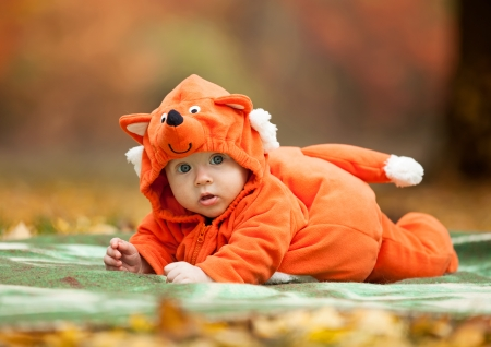Cute baby boy dressed in fox costume in autumn park photo