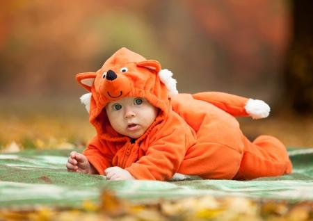 Schattige baby jongen gekleed in vos kostuum in de herfst park