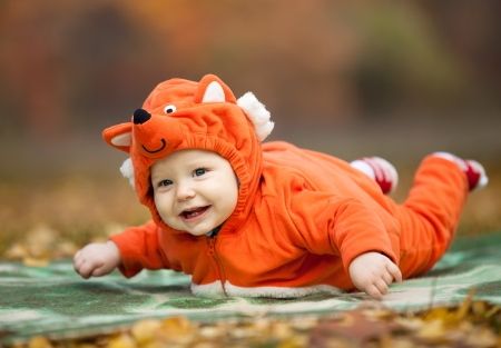Baby boy dressed in fox costume in autumn park photo