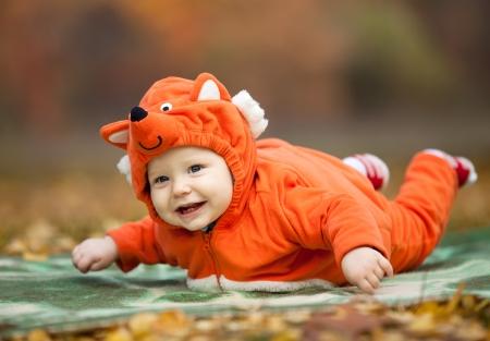 Bebé vestido en traje de zorro en el parque de otoño Foto de archivo